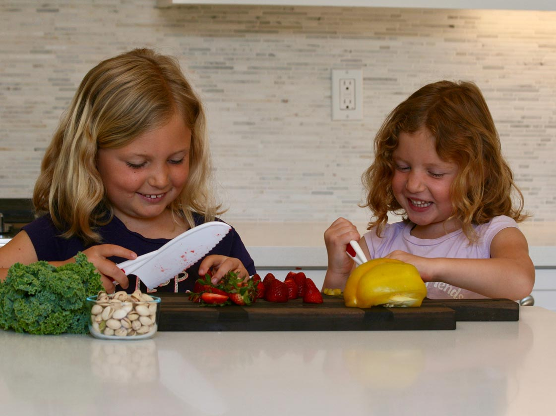 Kids chopping fruits and veggies in the kitchen