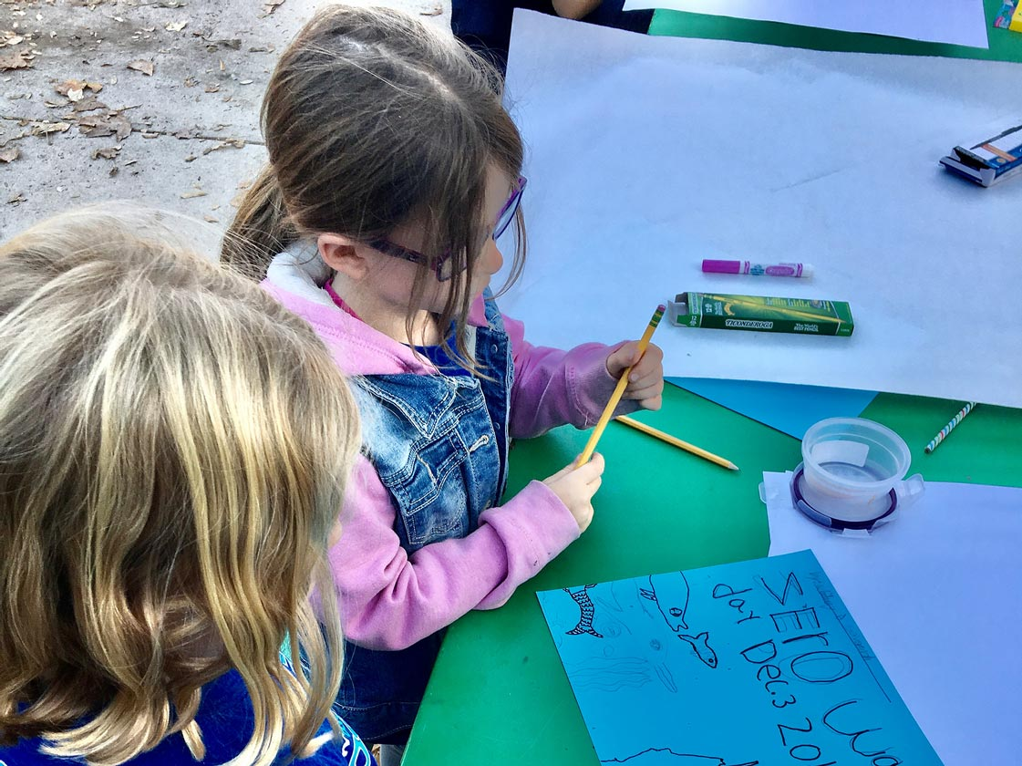Kids making a sign in favor of zero-waste lunch day at school.
